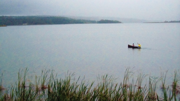 Raining in Flores. A couple is going home with their canoe to the other island.