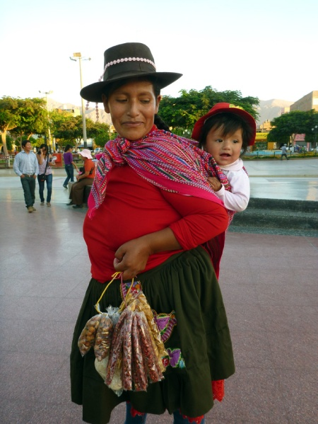 A woman and her kid in traditional clothing selling nuts and seeds. So sweet!