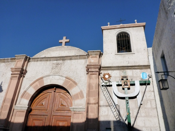 A church inside the walls somewhere in Arequipa... I find the cross on the right side really wierd. I've seen a few like these... why does it have a glass, hammer, a latter, a sword, and even an ear on it??? Haha.