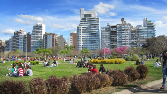 Rosario - high buildings behind and green park with a lot of picknick-people in front.