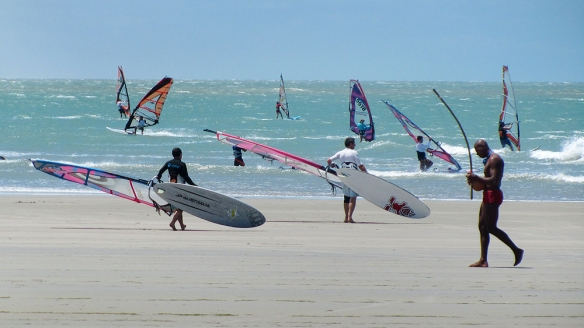 Windsurfers and a man playing capoeira-music