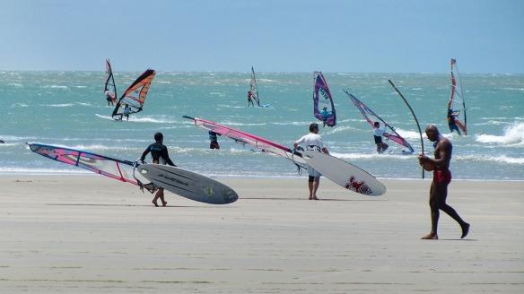 Windsurfers and a man playing capoeira-music
