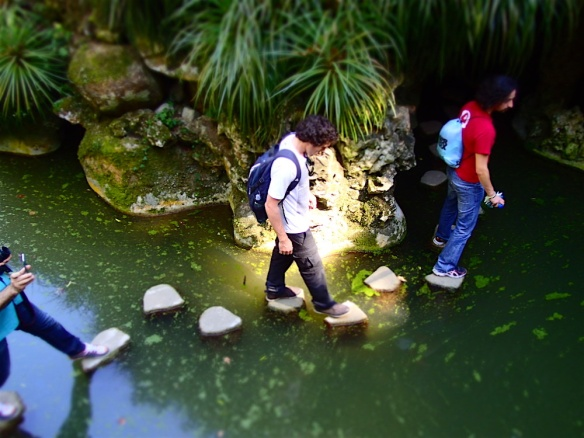 Crossing over a small river to get into a cave in Quinta de Regaleira
