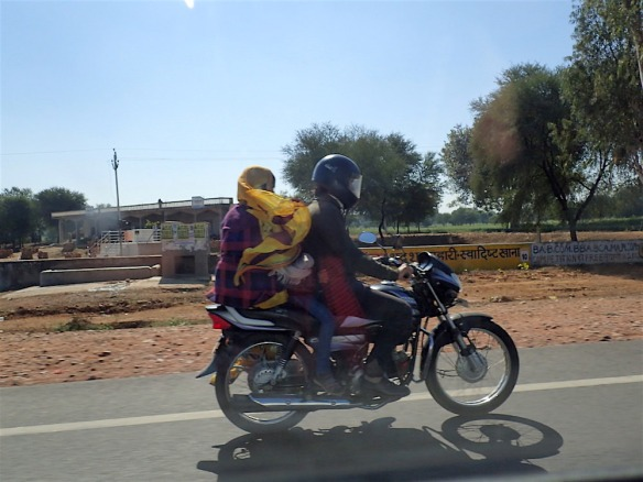 Woman with both her legs on the other side, and a kid there inbetween her and the driver