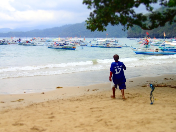 Our boat captain (he is so tiny!) picking up trash on the beach